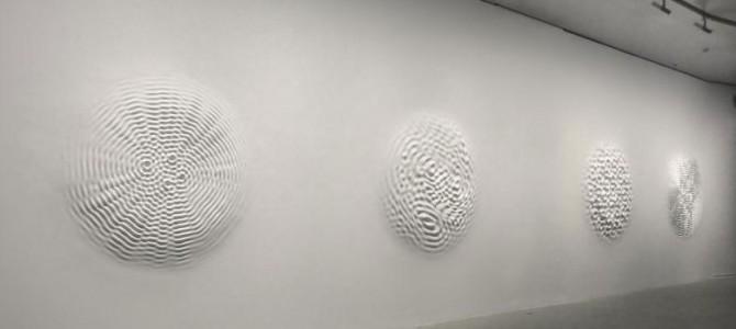 Loris Cecchini はギャラリーの壁に音でゆれる水面を生み出す